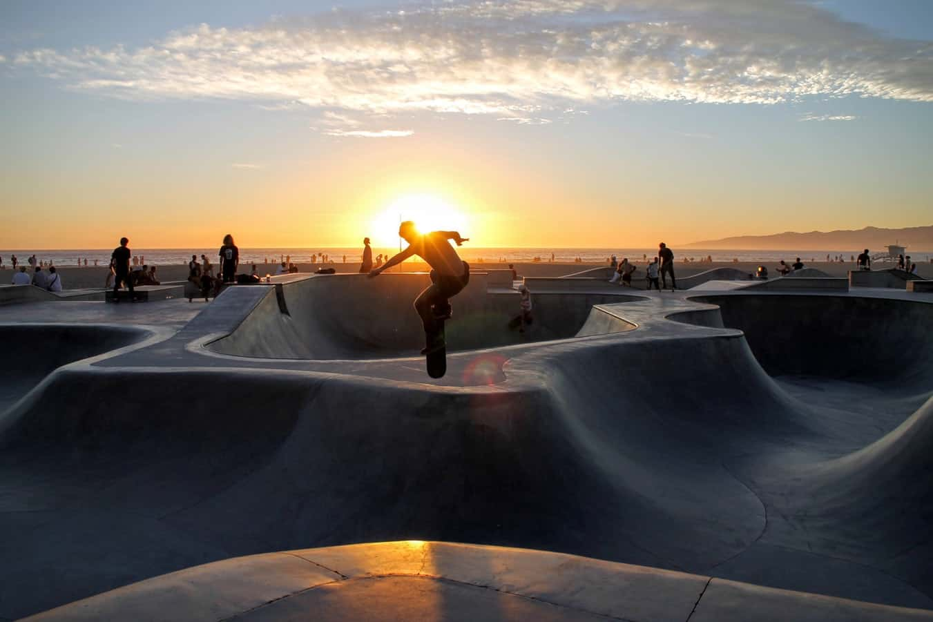 person on ramp riding skateboard with sun in the backround